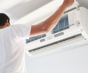 man performing maintenance on ac unit