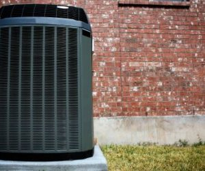 air conditioning system installed outside in front of brick wall