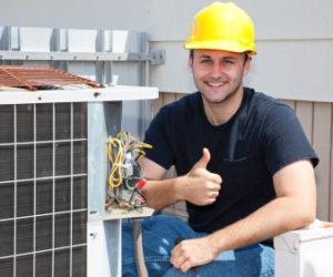 man smiling and posing in front of geothermal heating and cooling system outside
