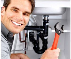 plumber smiling and holding a wrench in front of under sink