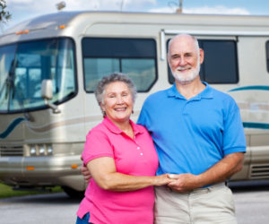 older couple holding hands and smiling in front of rv