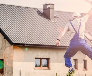plumber contractor jumping in air outside in front of house